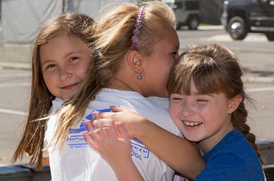 Photo of three Neighborhood Christian School student girls embracing and smiling