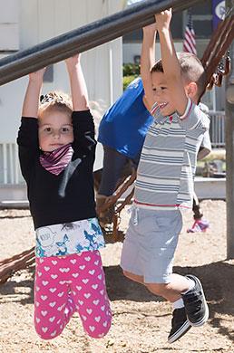 school children hanging from playground monkeybars