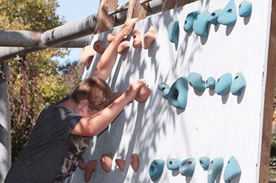 student climbing playground rock wall