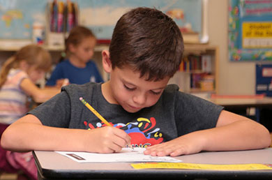 Photo of a young Neighborhood Christian School student boy sitting at his desk focused on completing his worksheet
