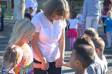 Photo of a Neighborhood Christian School teacher in a prayer circle with six of her students